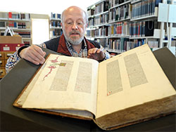 Archivar Thomas Bouillon mit einem Inkunabelband